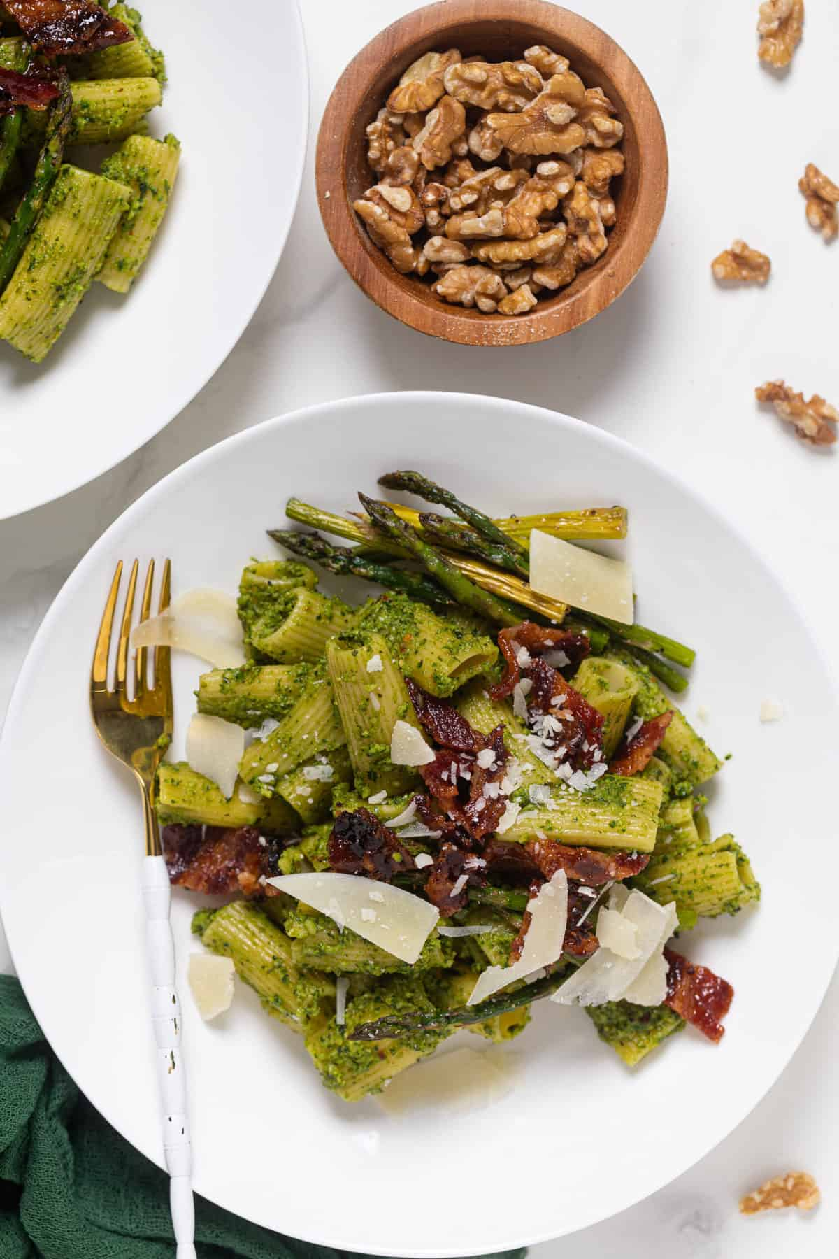 Pesto Pasta with Asparagus + Bacon on a white plate with a gold and white fork and walnuts on the side