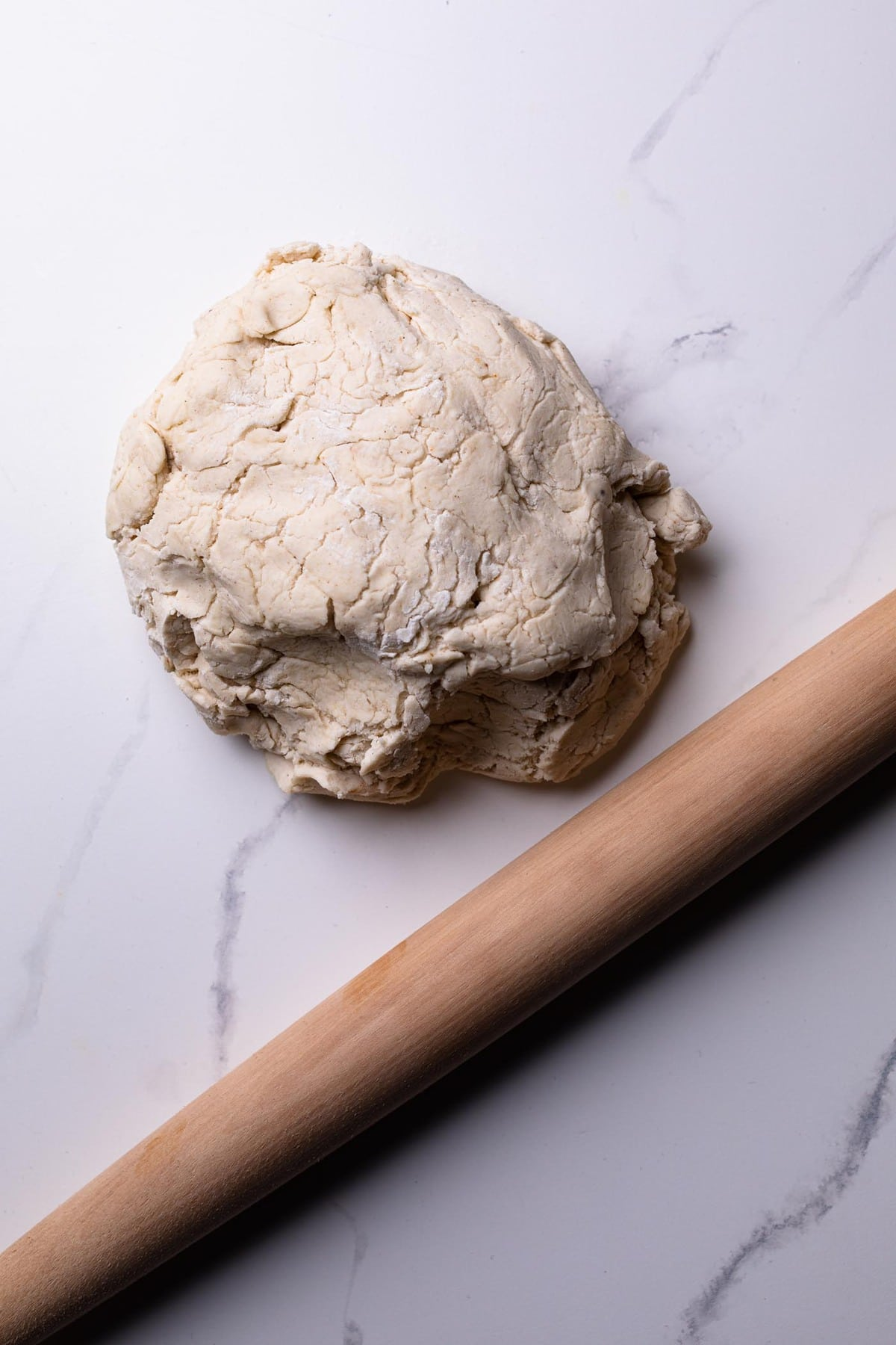 Easy Homemade Gluten-Free Pizza Crust in a ball on a counter with a wooden rolling pin