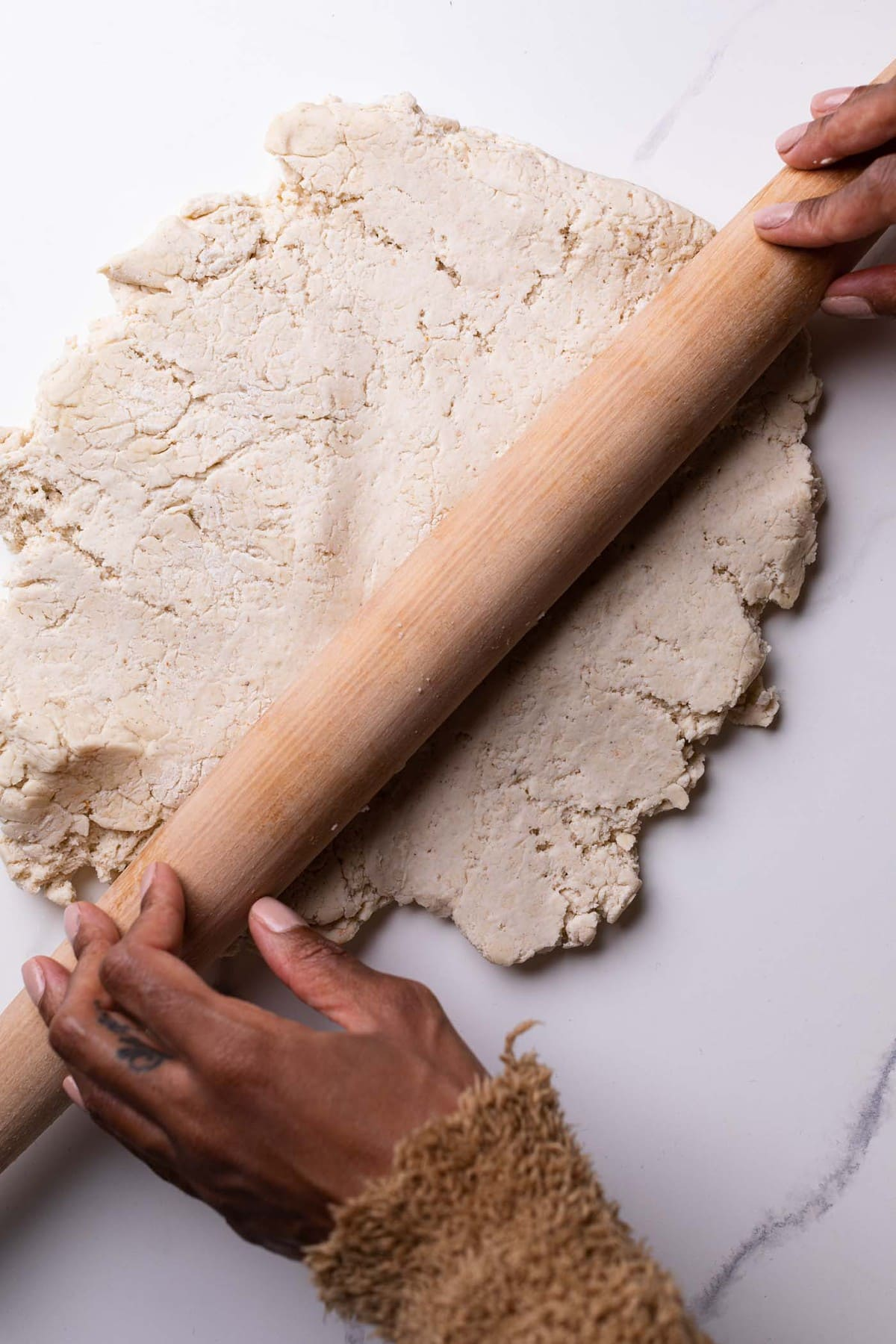 Easy Homemade Gluten-Free Pizza Crust being rolled out by a wooden rolling pin