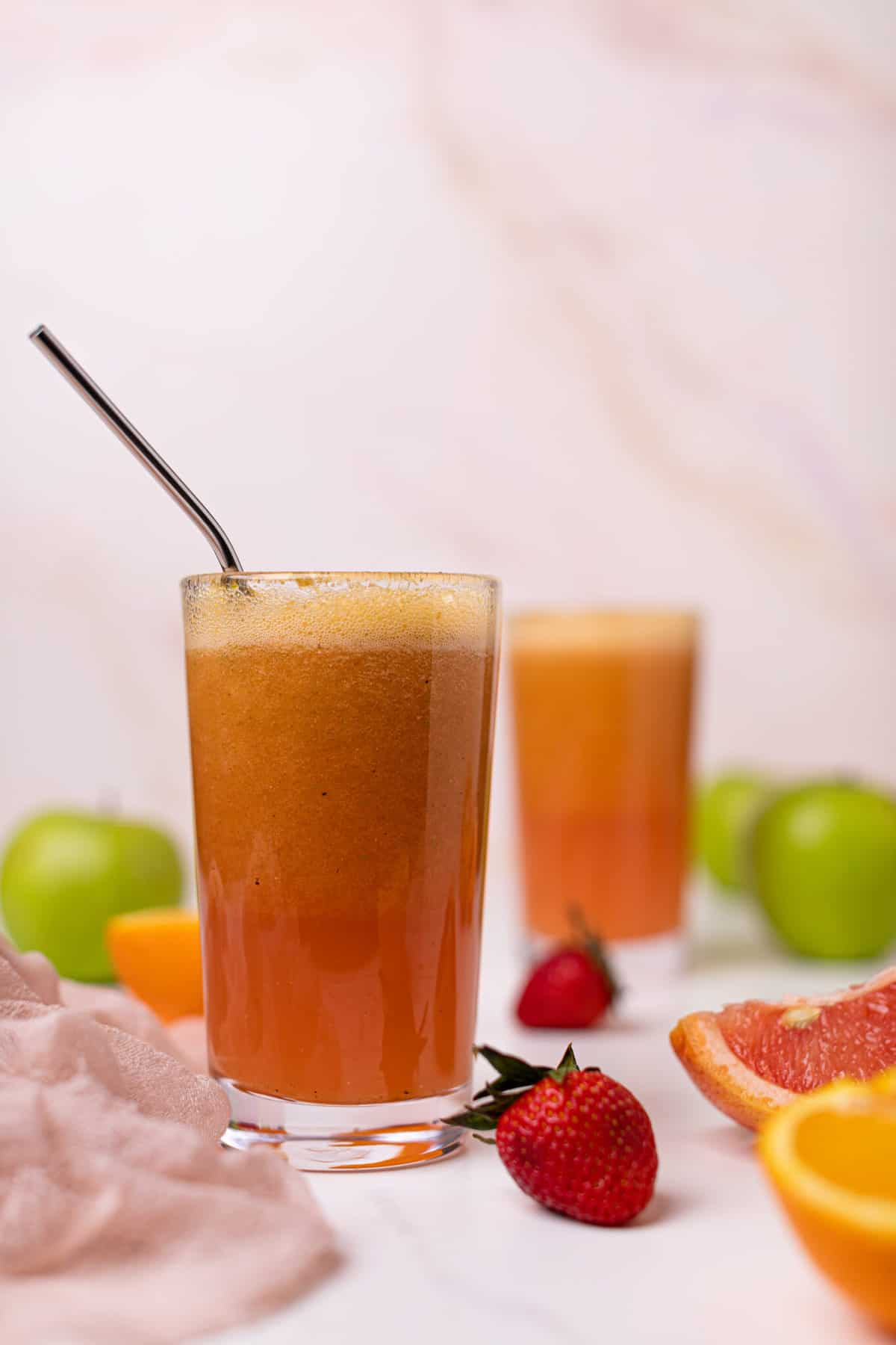 Apple Citrus Strawberry Juice in two glasses with a metal straw and fresh fruit