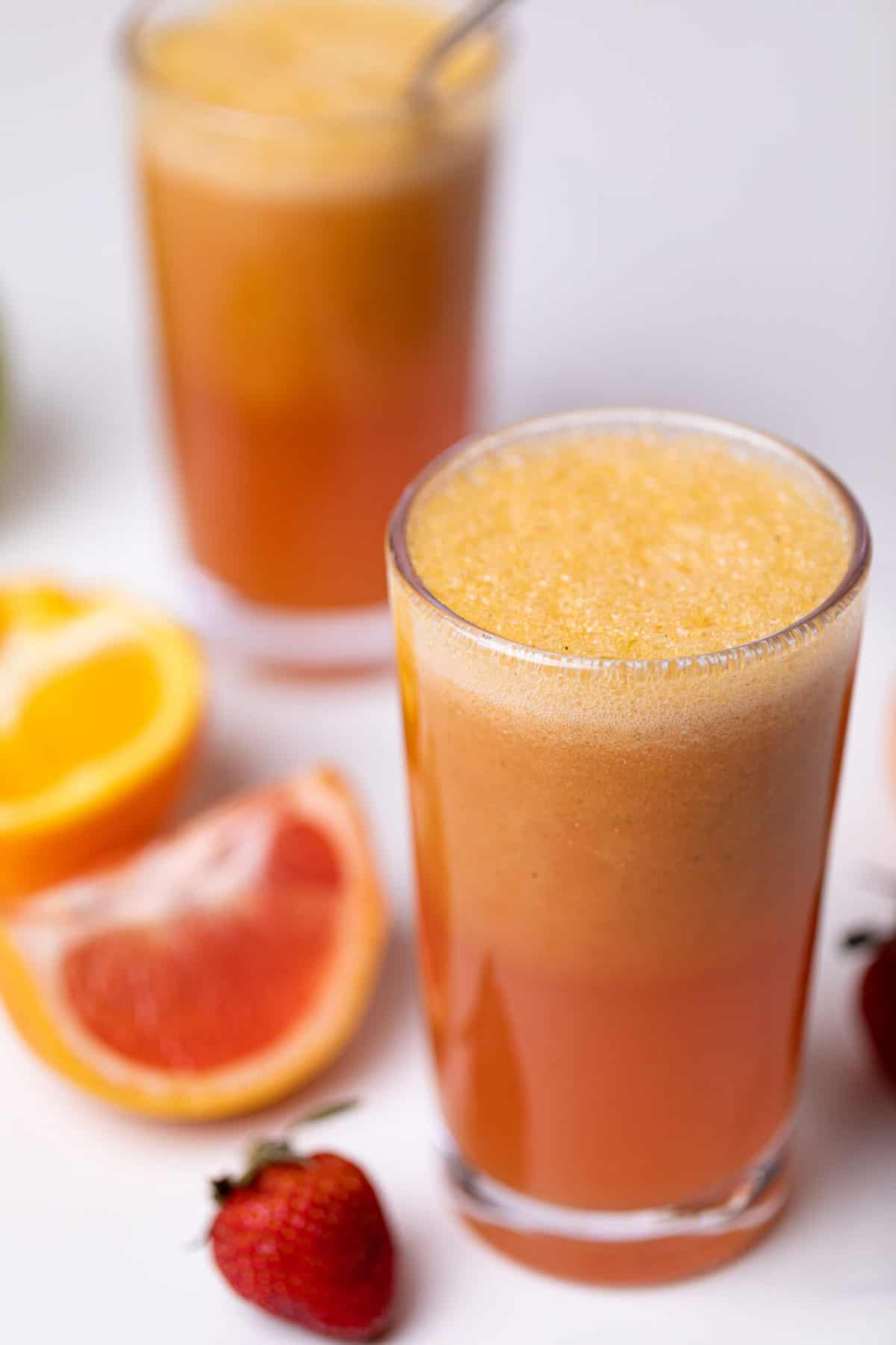 Apple Citrus Strawberry Juice in two glasses with fresh fruit