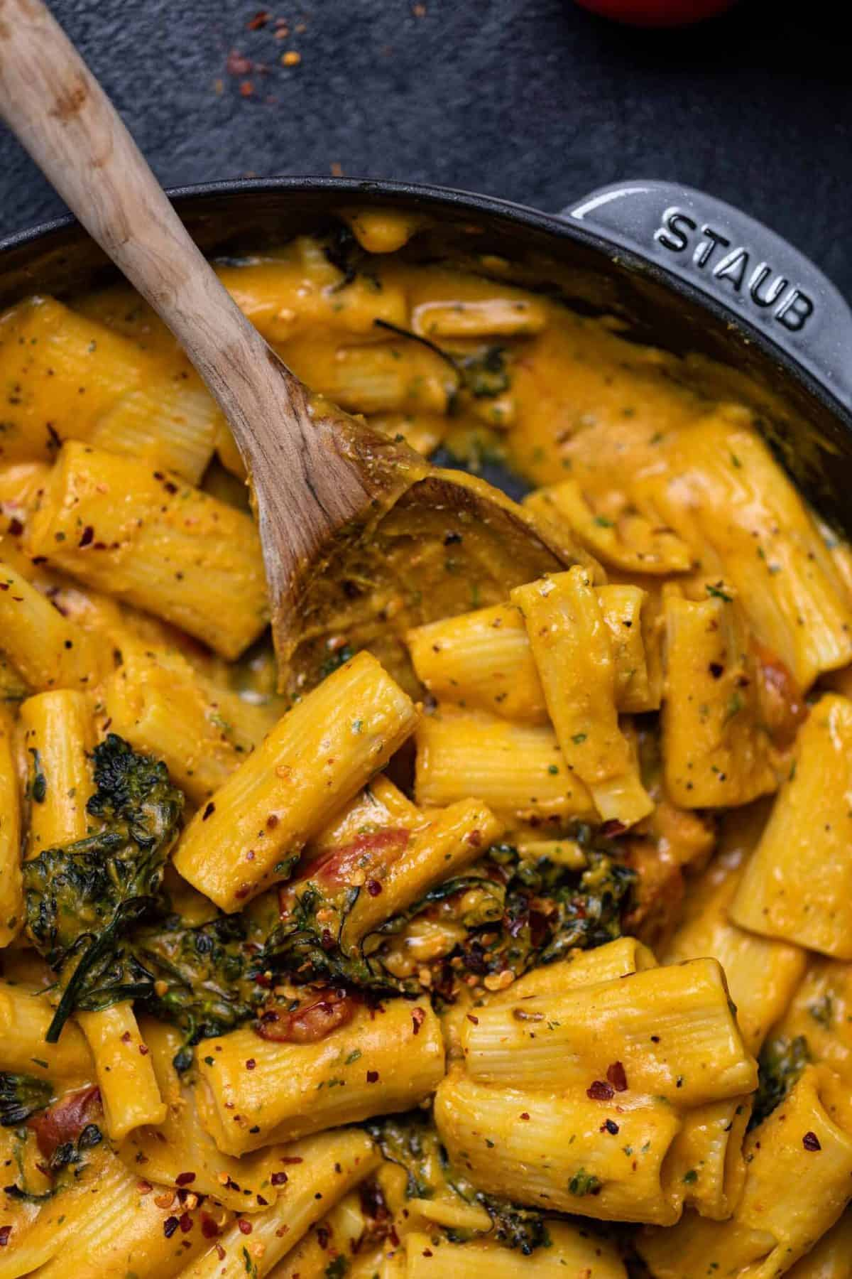 Vegan sweet potato pasta skillet with roasted broccolini in a cast iron pan close up