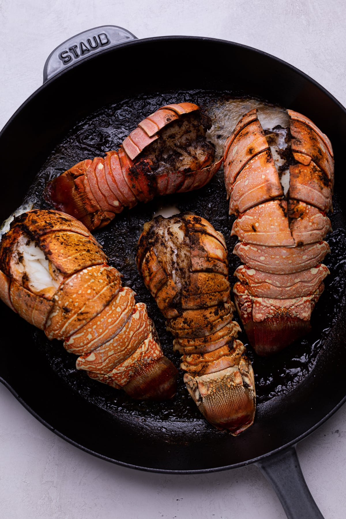 cast iron skillet with four lobster tails cooking