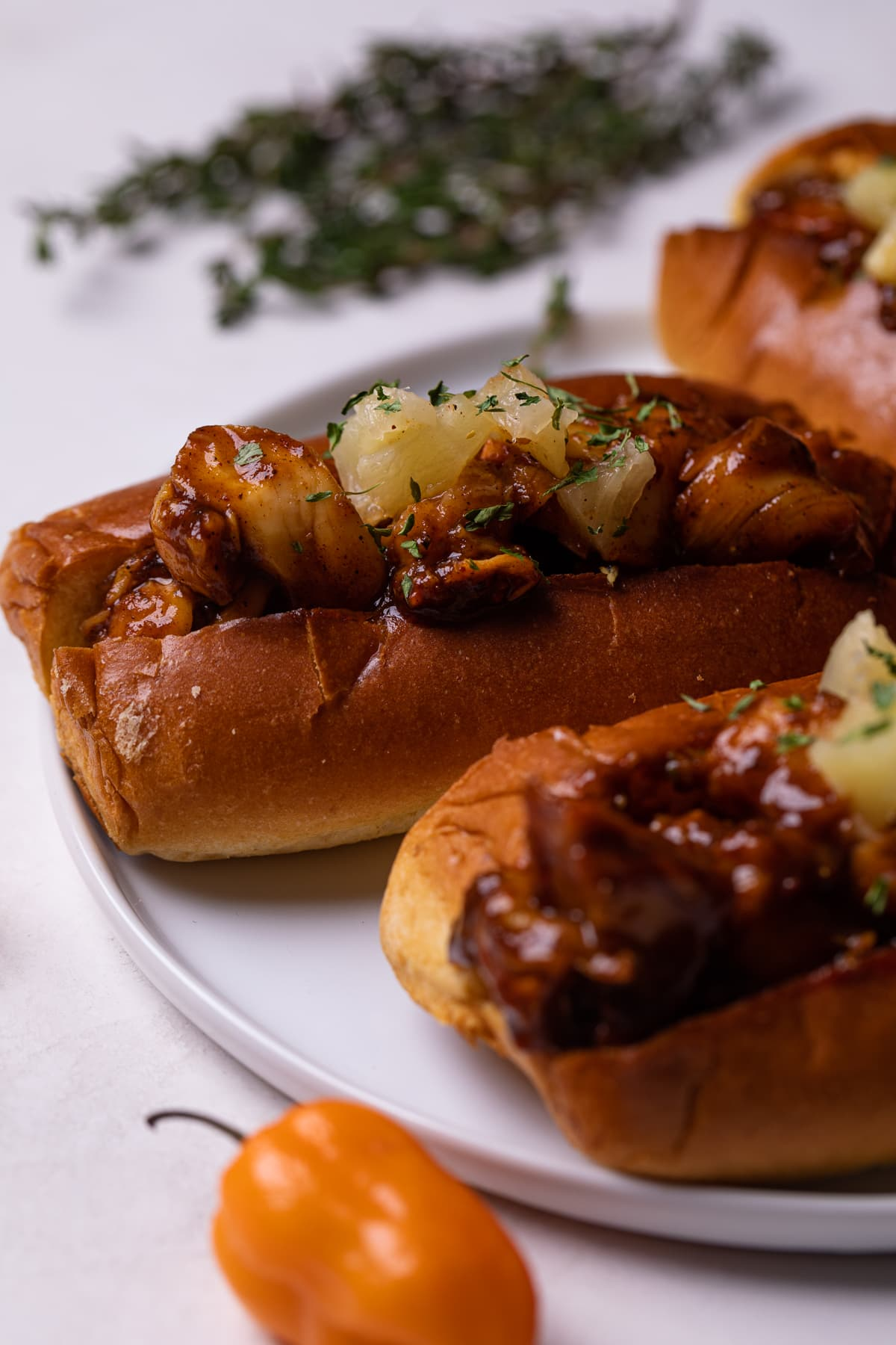Spicy + Sweet BBQ Jerk Lobster Rolls on a white plate