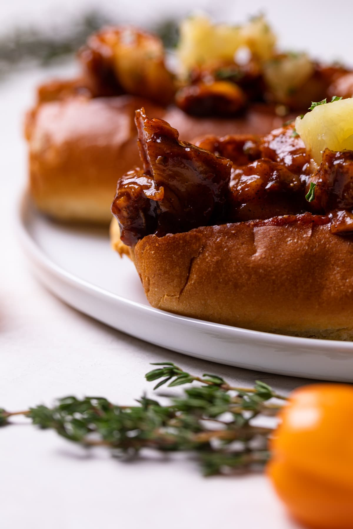 Spicy + Sweet BBQ Jerk Lobster Rolls on a white plate with fresh thyme
