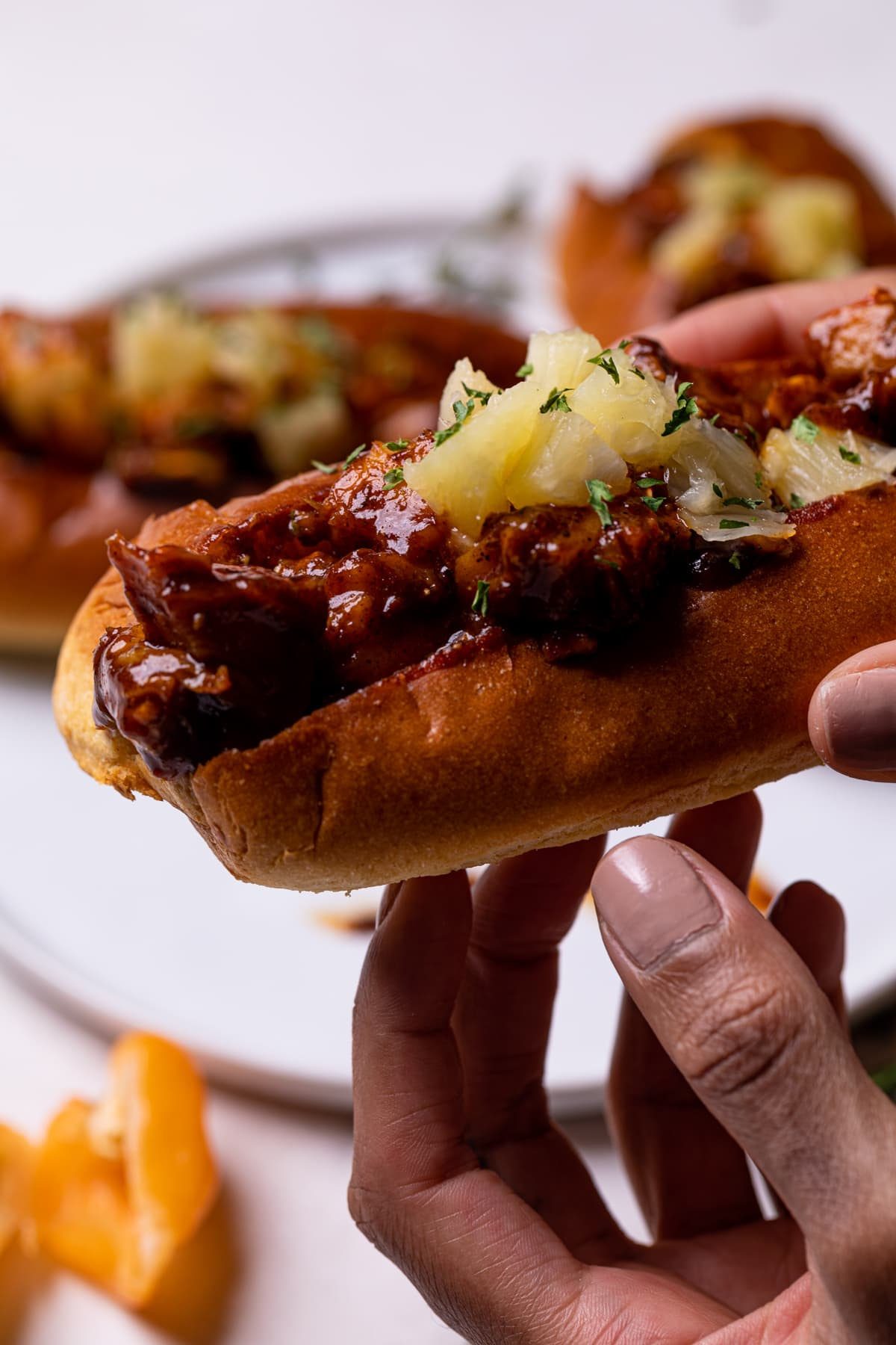 Spicy + Sweet BBQ Jerk Lobster Rolls in a woman's hand with pineapple on top