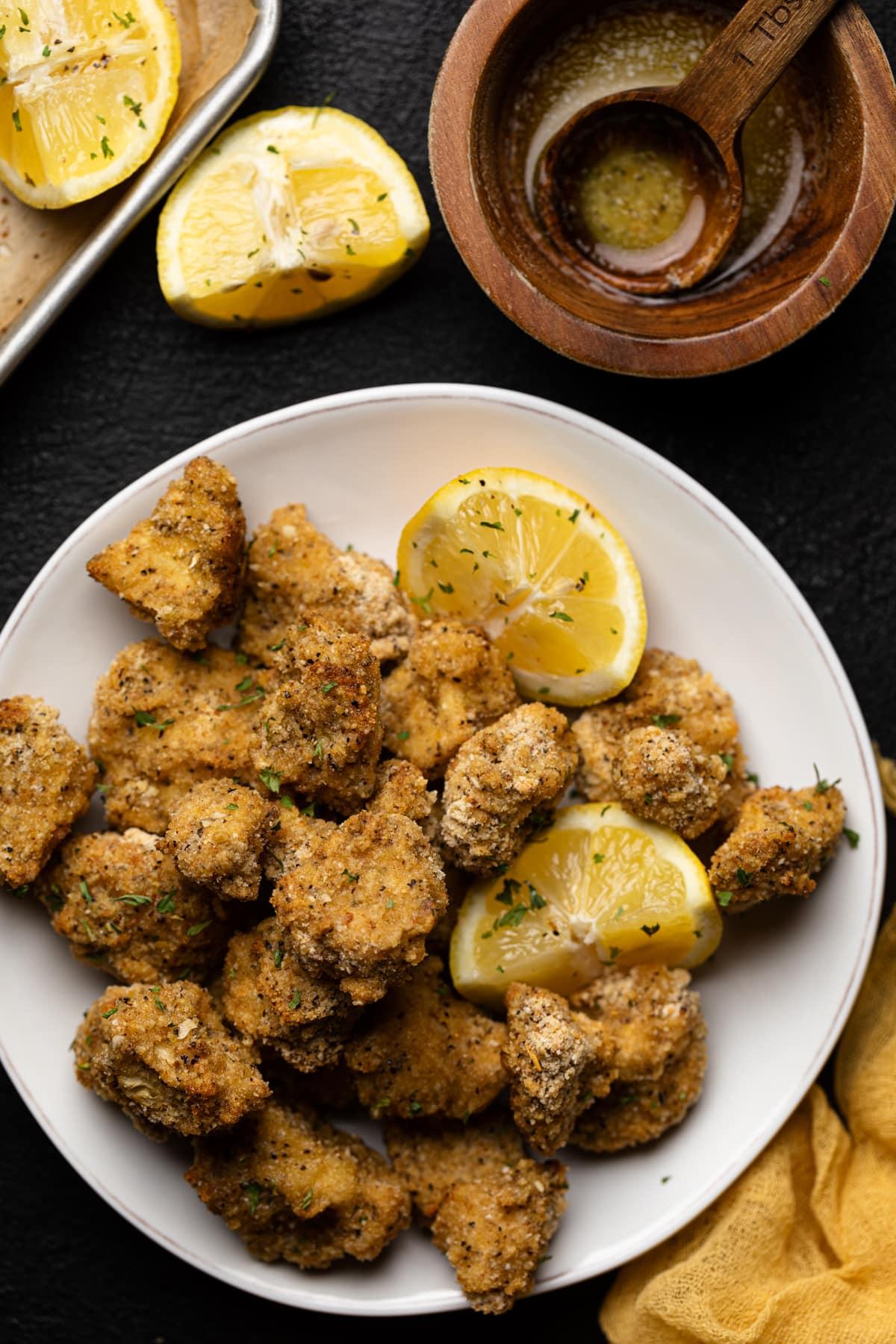 Lemon Pepper Cauliflower Bites on a plate with lemon wedges