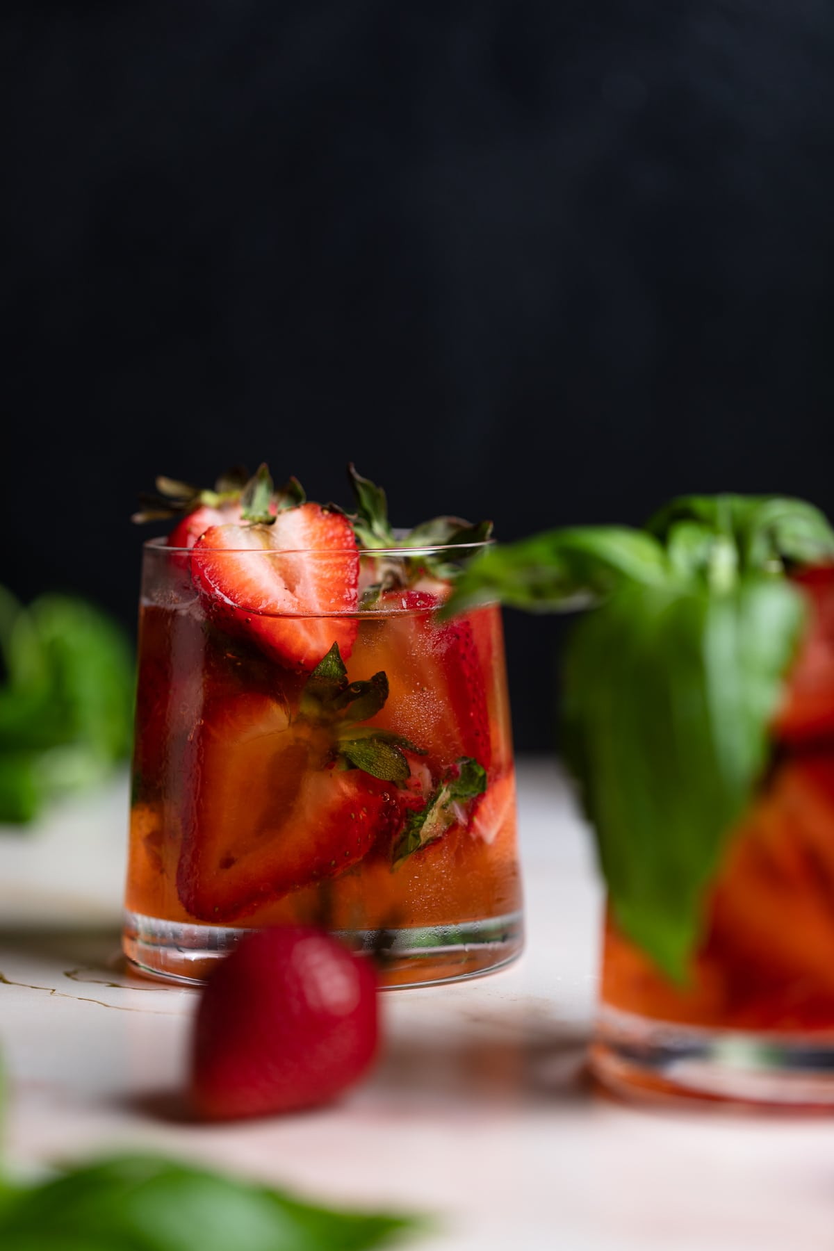 Strawberry Basil Pineapple Mocktail in a glass with fresh strawberries and basil