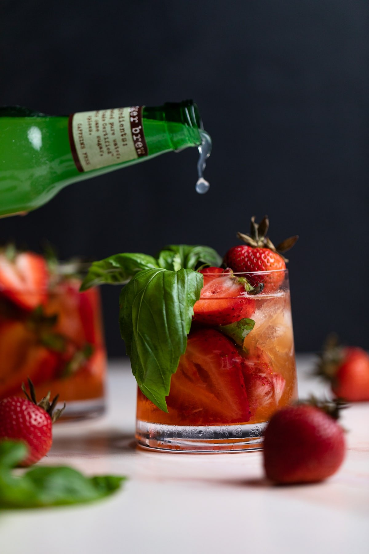 Strawberry Basil Pineapple Mocktail in a glass with fresh strawberries and basil pouring in ginger beer