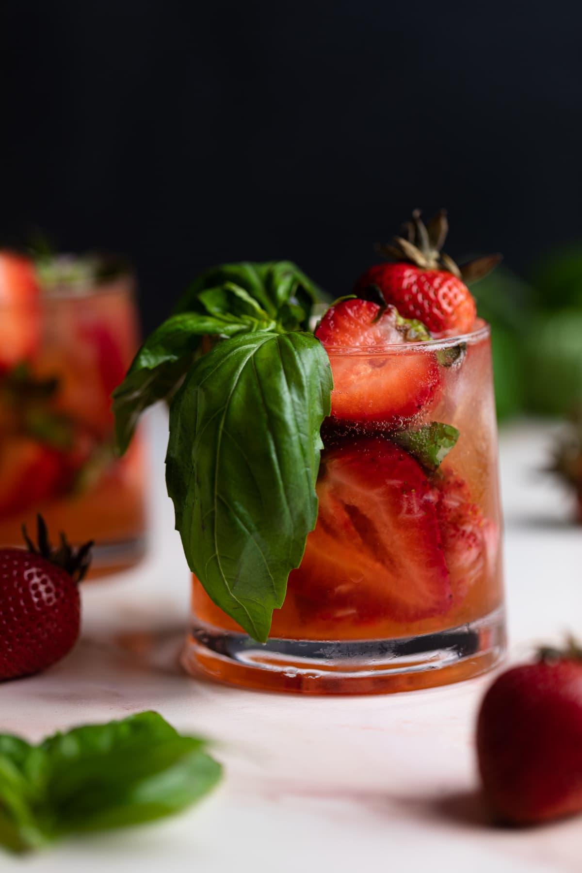 Strawberry Basil Pineapple MocktailStrawberry Basil Pineapple Mocktail in a glass with fresh strawberries and basil